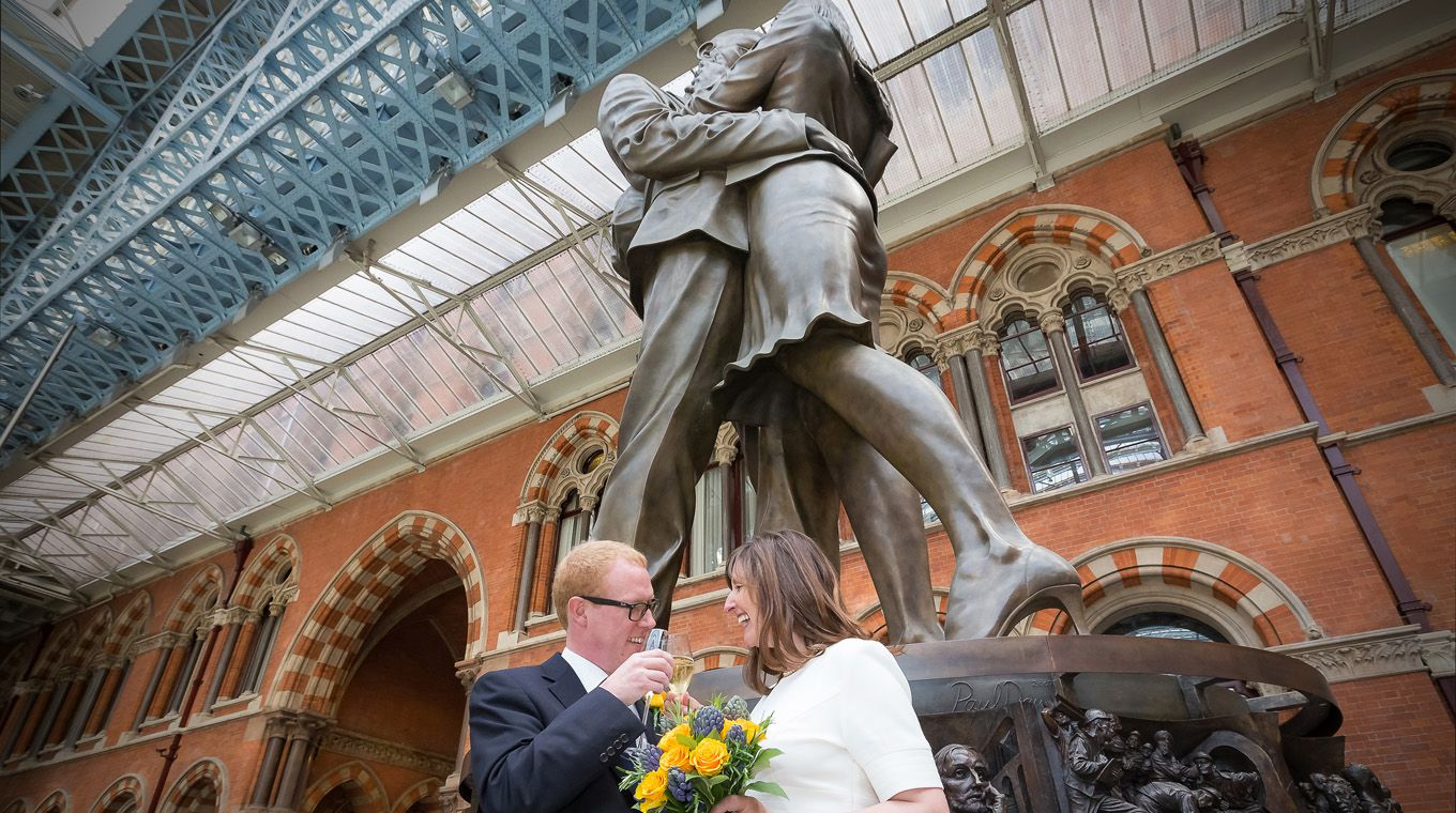 Just married couple by The Meeting Place statue at St Pancras Station, London