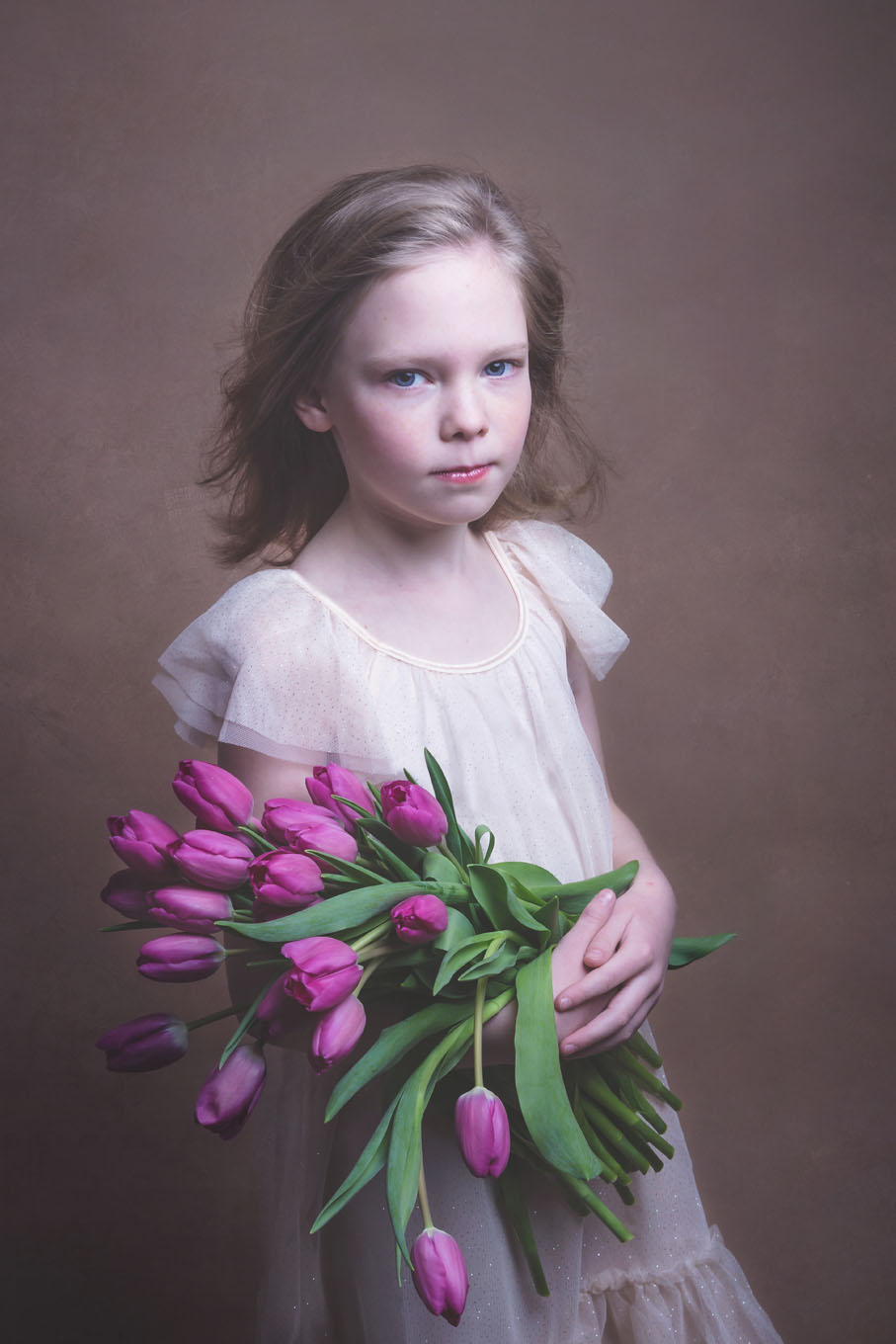 Portrait of a little girl in a studio with backdrop and lighting equipment